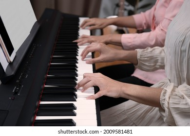 Two woman playing paino together, fingers press on key board, smartphone and paper blank note on paino holder. Relaxing, practicing learning music.
