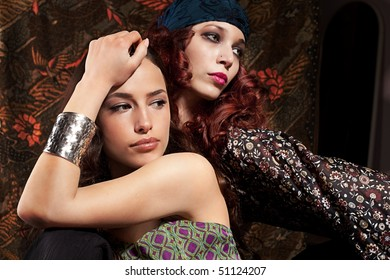two woman, red and black hair