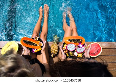 Two woman relaxing on luxury tropical vacation holding big plates with different tasty sweet exotic fruits, travel and eating healthy, vegan vegetarian lifestyle, slim long legs, diet concept.