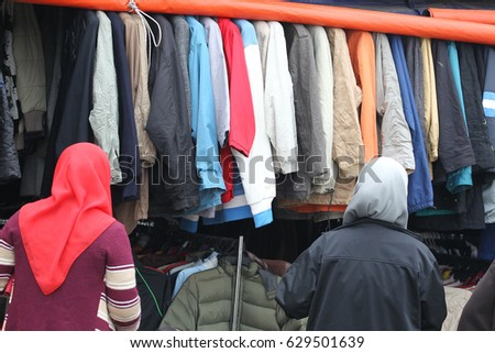 af233aa9644 Two woman shopping for used winter clothing at street market in Kundasang  Sabah. Used clothes
