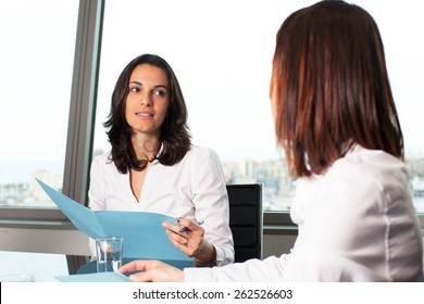 Two woman sitting at a table in office during job interview