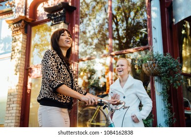 Two woman in small town downtown America laughing.