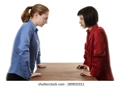 two woman stand over a table not looking very happy