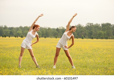 two woman stretching outdoors