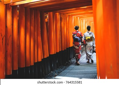 two woman walking through famous lines of orange column Tori at Fushimi Inari Temple, Kyoto Japan