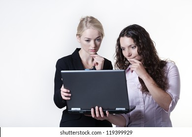 two woman work colleagues looking at something on a laptop screen