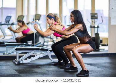 two woman working out together in gym doing squats