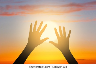 Two woman's silhouette hands on the beautiful sunset sky above the sea. The image depictures the concept of hope, faith, religion, life, relationship, love, friendship and care.