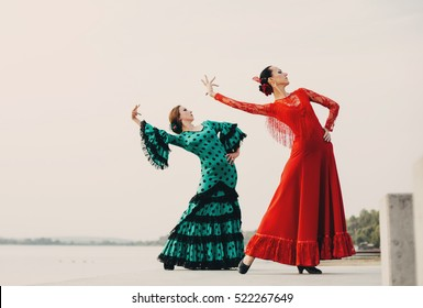 two womans traditional dancer wearing colorful dress on the beach