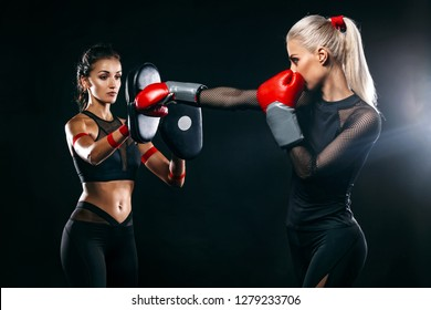 Two women athlete and boxer trainging before fight on black background. Sport and boxing concept.