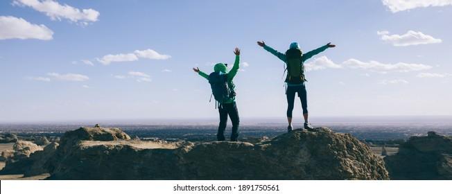 Two women backpackers hiking on sand desert