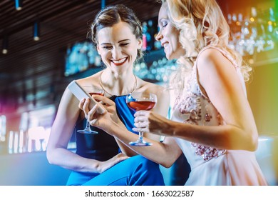 Two women in a bar looking at their mobile phone having fun