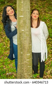 Two women behind tree in the forest having fun