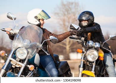 Two women bikers greeting each other with fists blow, usually gesture for motorcyclists