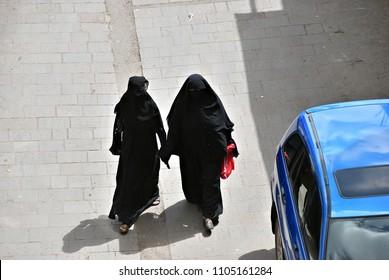 Two women in a black burka Burqa walking down a middle eastern road