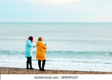 Two women in bright clothes are standing on the beach, admiring the view. Rear view. The concept of outdoor recreation.