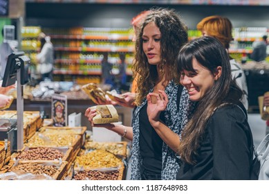 two women buying dried fruit in grocery store. lifestyle