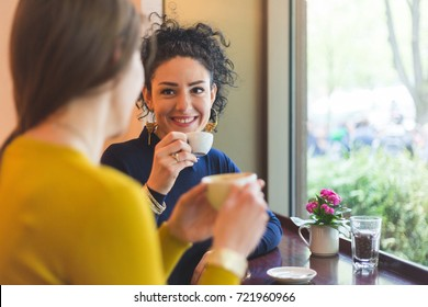 Two women in a cafe smiling and drinking coffee together. Friends or lesbian couple having a break and enjoying a coffee in the city.