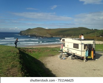 Two women with a caravan, surfboards and camping equipment taking photos during their road trip along the atlantic coast at Playa Pantin, Spain in October 2016.