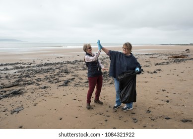 Two women celebrating after picking up rubbish on the beach