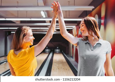 Two women celebrating bowling strike with high five