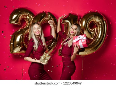 Two women celebrating at new year party happy laughing girls in casual dresses throw gold stars confetti having fun with 2019 balloons on red background