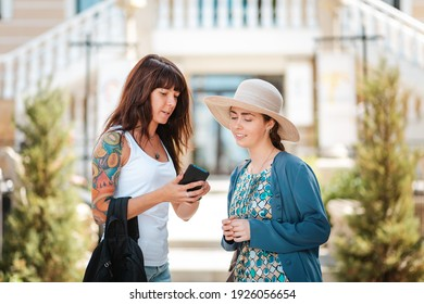 Two women are chatting on the street, engrossed in something on their smartphone. The concept of communication and modern technology.