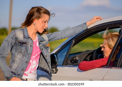 Two women chatting at the roadside with a young woman leaning against a car chatting to the female driver, close up view