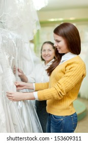 Two women chooses wedding outfit at shop of wedding fashion