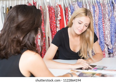 Two women choosing clothes from a catalogue in a shop