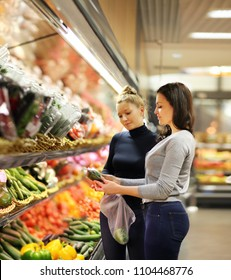Two women choosing a vegetables at supermarket