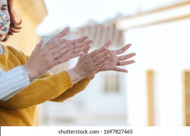 Two women clapping on the balcony
