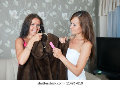 Two women cleaning fur coat  with whisk broom at home