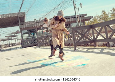 Two women in coats jump and play hopscotch on the pavement