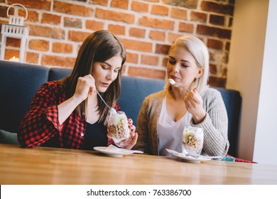 Two women consuming sweet healthy dessert in a restaurant, talking and spending time together. Clean eating.