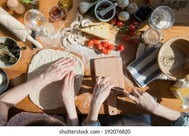 Two women cooking pizza at home. Filling pizza with ingredients. Top view. Overhead view.