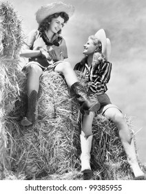Two women in cowboy hats sitting on a haystack