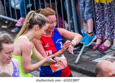 Two women cross the finishing line of the 2017 Liverpool Rock n Roll half marathon and immediately pause to check their finishing times on their watches.