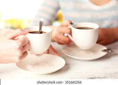 Two women with cups of coffee on bright background