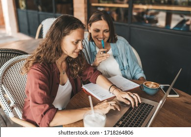 Two women discussing business projects in a cafe while having coffee. Startup, ideas and brain storm concept
