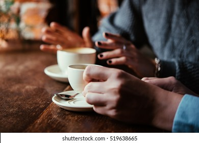 Two women discussing business projects in a cafe while having coffee