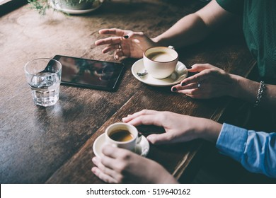 Two women discussing business projects in a cafe while having coffee. Toned picture