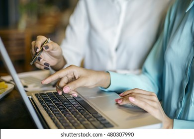 two women discussing and pointing to a laptop