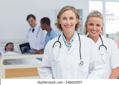 Two women doctors standing and looking at the camera in front of medical team and patient