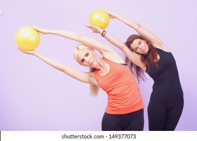 Two women doing Pilates exercise with stability ball