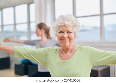 Two women doing stretching and aerobics workout at gym. Senior woman with her trainer in background during physical training session