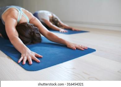 Two women doing stretching workout on fitness mat. Females performing yoga on exercise mat at gym. Child Pose, Balasana.