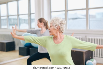 Two women doing stretching and yoga workout at gym. Female trainer in background with senior woman in front during physical training session