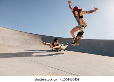 Two women doing stunts on skateboards at skate park. Female friends practising skateboarding outdoors.