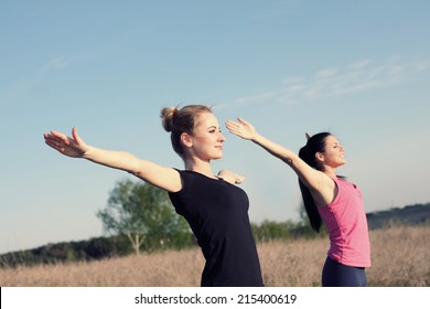 Two women doing yoga outdoors. yoga instructor shows poses